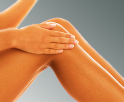 Woman Rubbing a Lanolin Based Skin Moisturizer on Very Smooth Legs